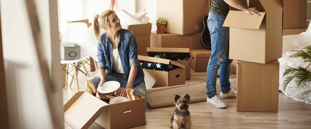Young couple moving with boxes into new place