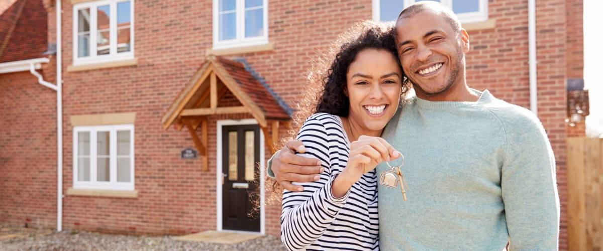 Portrait Of Couple Holding Keys Standing Outside New Home with Keys