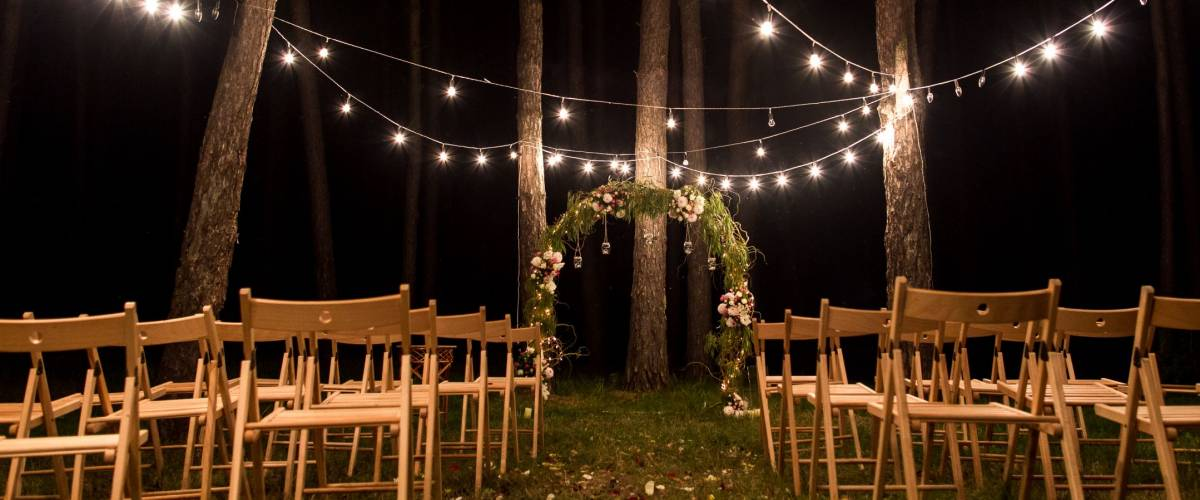 Night wedding ceremony. Decorations for wedding ceremony with chairs, arch and lamps in the night forest