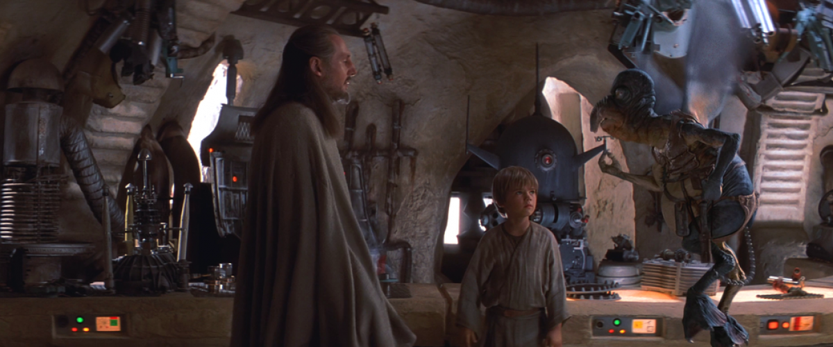 Qui-Gon Jinn negotiates with Watto as Anakin Skywalker looks on from Star Wars Episode I