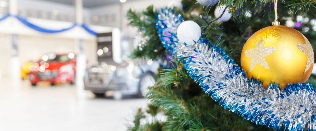 colored christmas balls on branch christmas tree in showroom with new car in the background - When Is The Best Time To Buy Christmas Decorations
