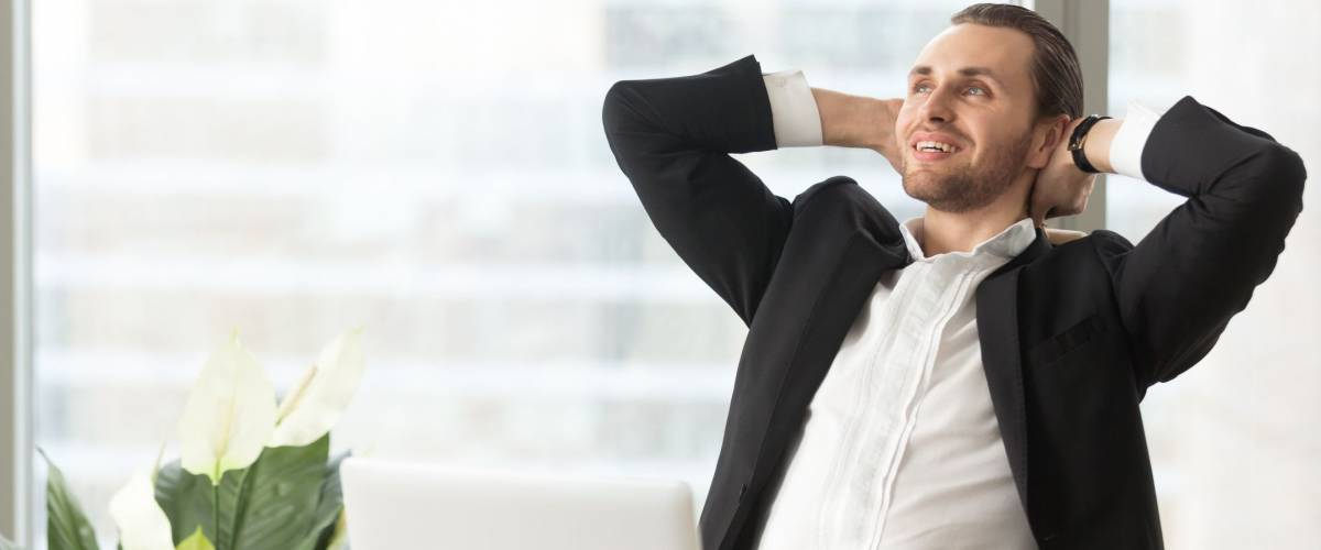 Happy smiling businessman relaxing, stretching his back with hands resting behind head