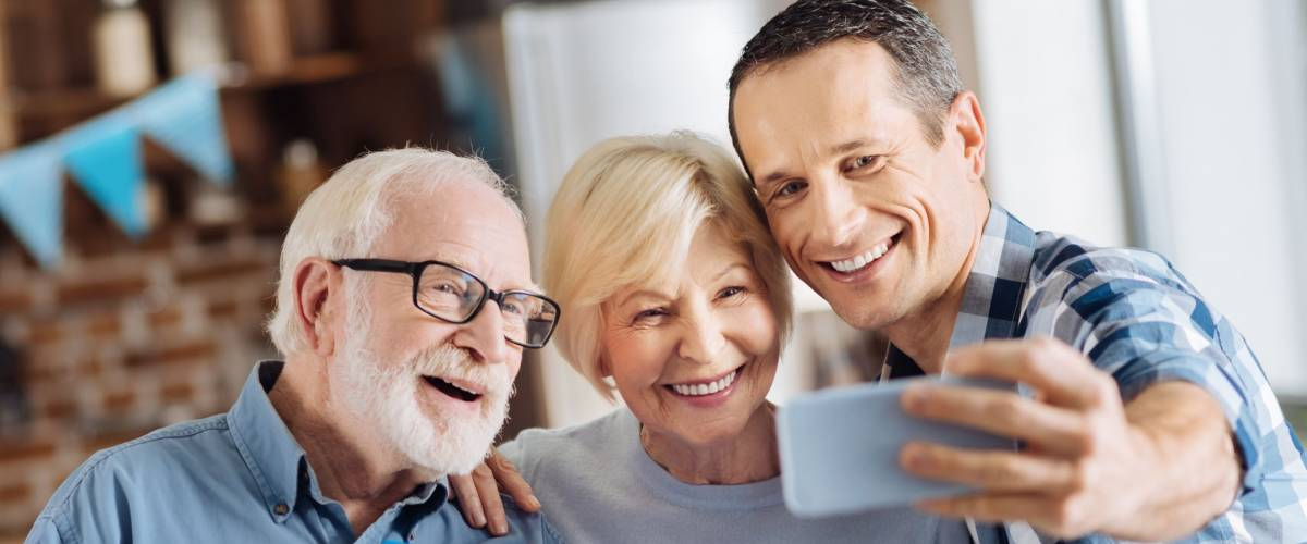 Seizing the moment. Cheerful young man taking selfies with his elderly parents during the celebration of the fathers birthday while the man holding a gift box