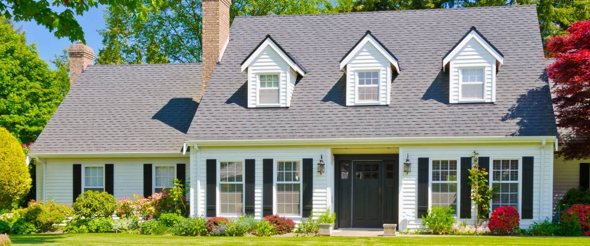 Custom built luxury house with nicely trimmed and landscaped front yard, lawn in a residential neighborhood. Vancouver Canada.