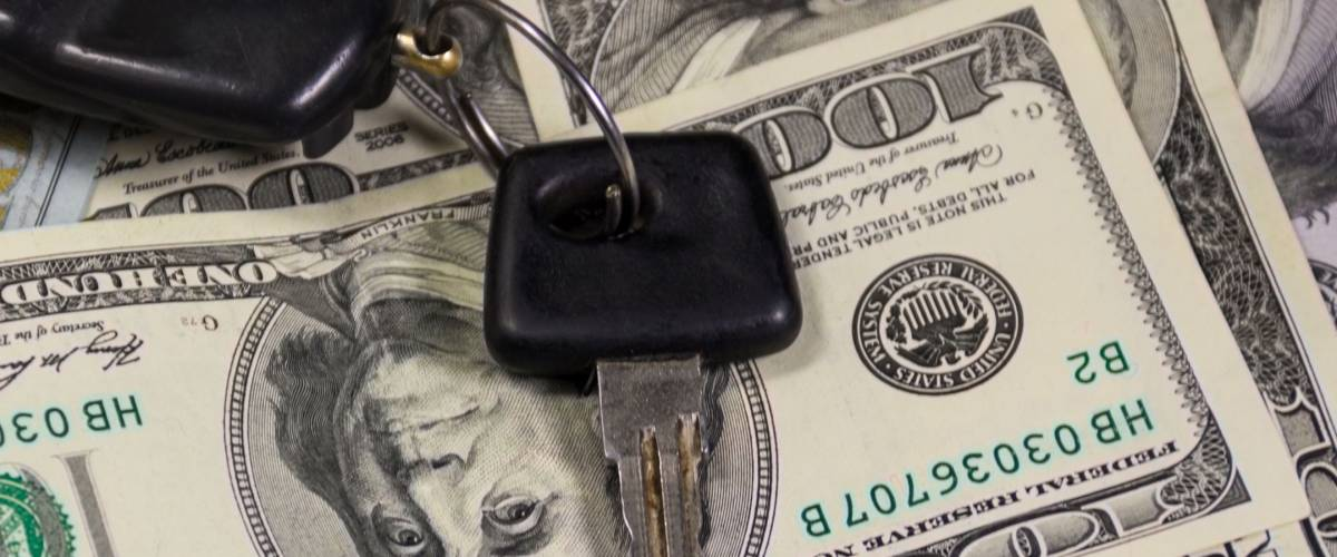Key with car key ring on background of American one hundred dollar bills. Concept of buying and selling a car
