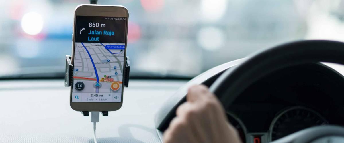 Primo piano della mano della persona sul volante dell'auto, utilizzando il cellulare per il GPS