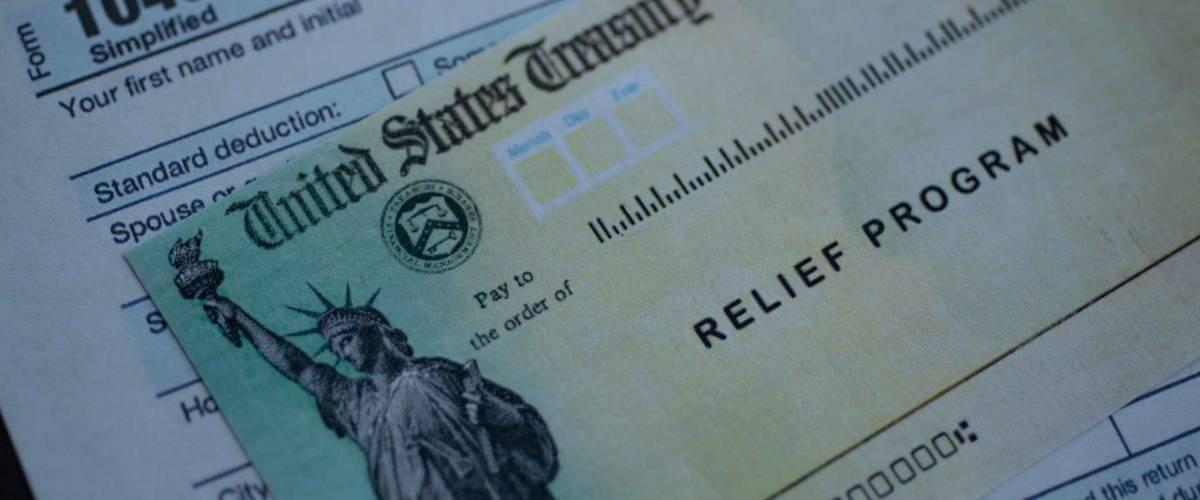 Modulo 1040 Dichiarazione dei redditi delle persone fisiche negli Stati Uniti accanto al programma Stimulus Check Relief. Vista ravvicinata.