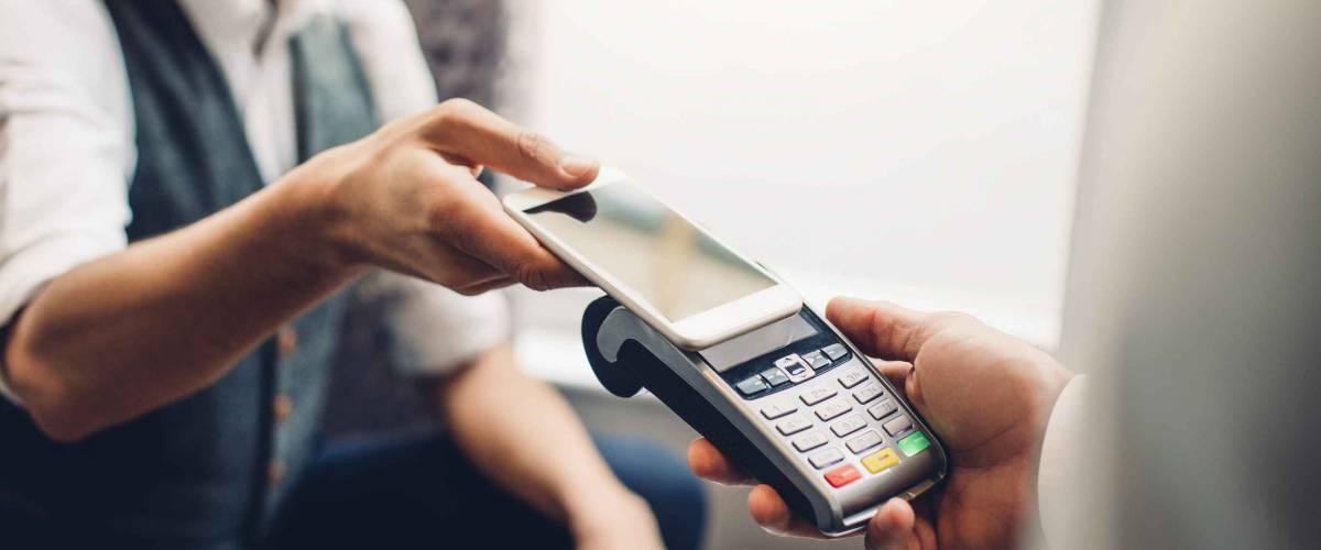 Uomo che usa il suo telefono per pagare, toccando la macchina interac
