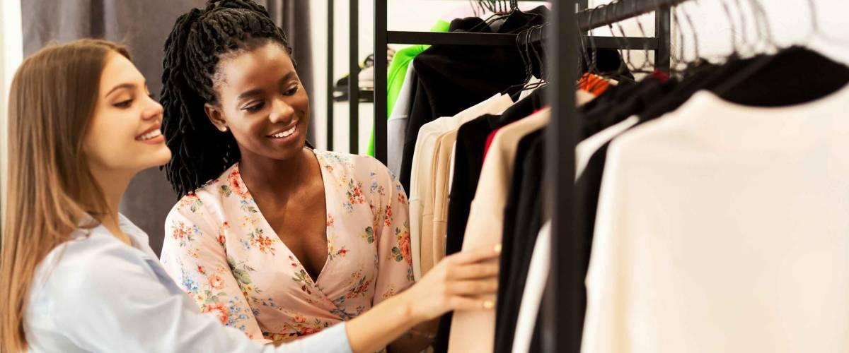 Due donna sorridente, sfogliando gli scaffali dei vestiti