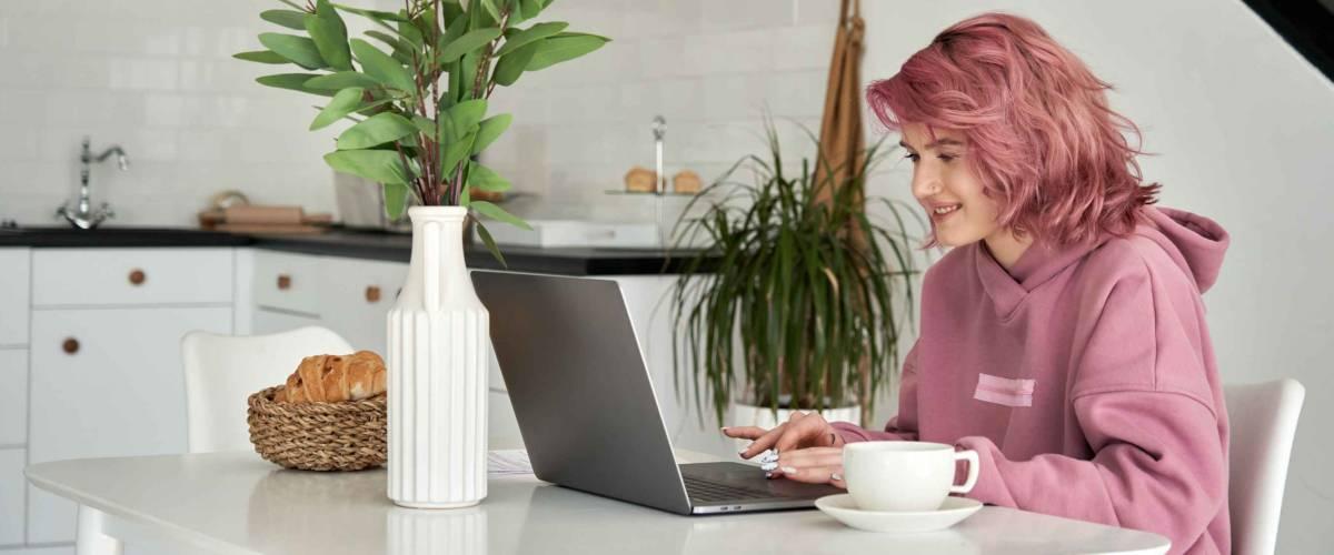 Giovane donna seduta al tavolo della cucina, lavorando al computer portatile