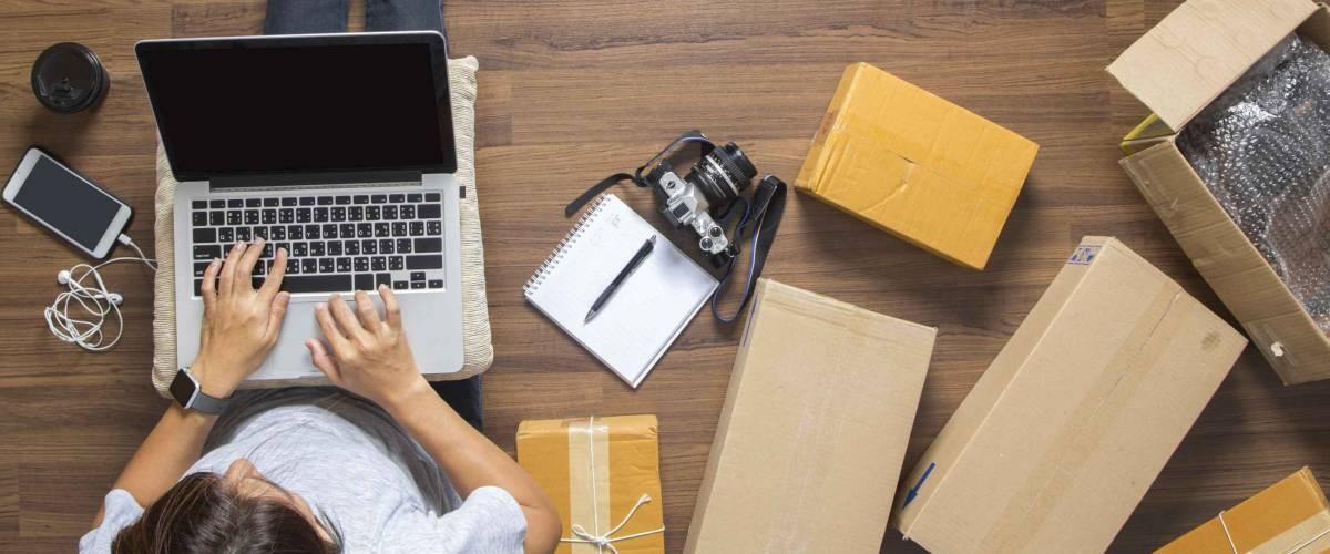 Vista dall'alto di donne che lavorano al computer portatile da casa sul pavimento di legno con i pacchi intorno a lei