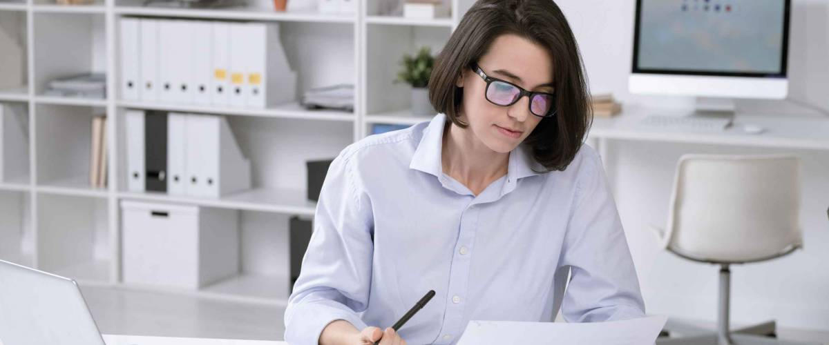 Young woman looks at sheet of paper while sitting at desk