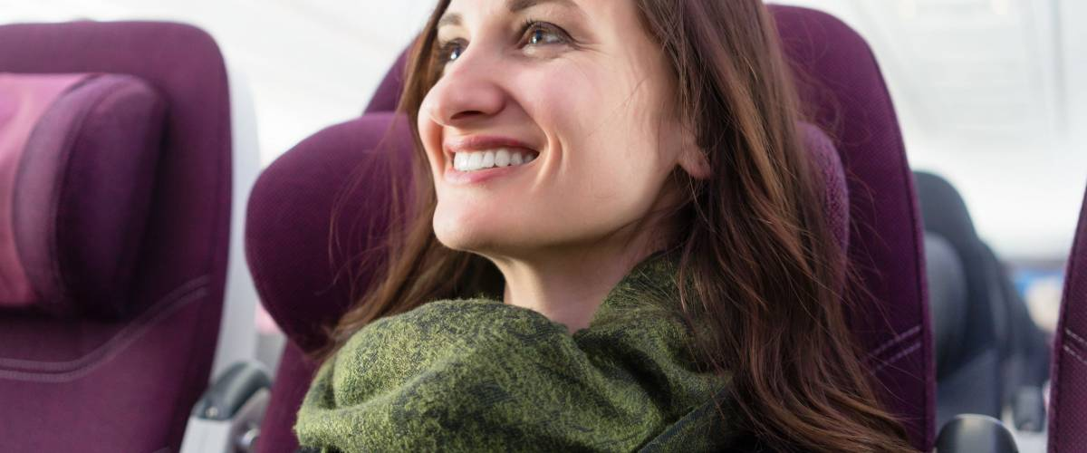 Happy woman with green scarf during flight in airplane