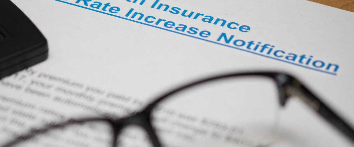 NOTICE OF INCREASING IN PREMIUM RATE OF HEALTH INSURANCE WITH A PAIR OF GLASSES AND A CALCULATOR