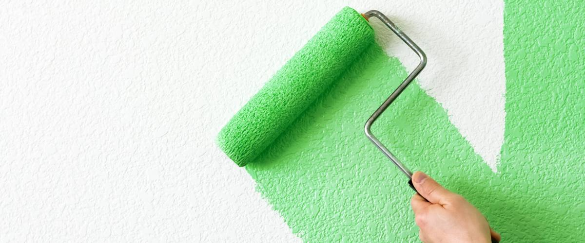 Person using a roller to apply green paint to a wall