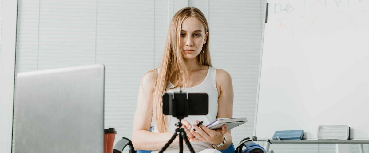 Side hustle, earn extra, money making, side job, side money, second job, hustling, hustle gig, gig economy concept. Young woman speaking in front of camera for vlog blog, recording video