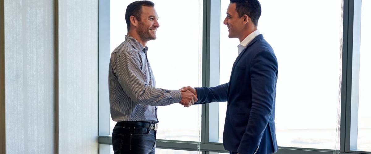Two smiling businessmen shaking hands together while standing by windows in an office boardroom overlooking the city