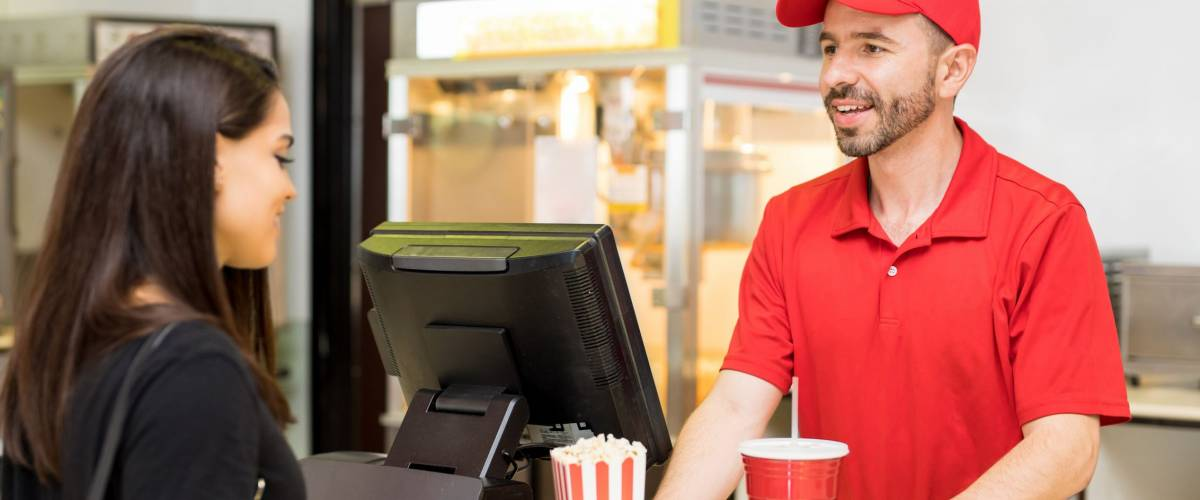 Portrait of a good looking worker in a concession food in a movie theater serving popcorn and soda to a female customer