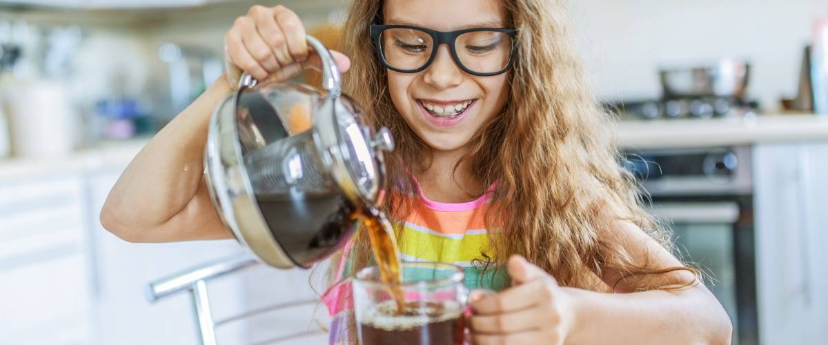 Little beautiful smiling girl in glasses pours tea from teapot into cup at kitchen table.