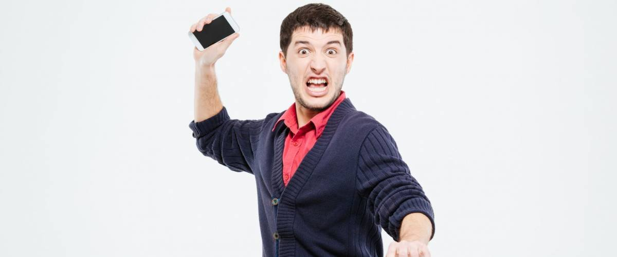 Angry man throwing phone into camera isolated on a white background