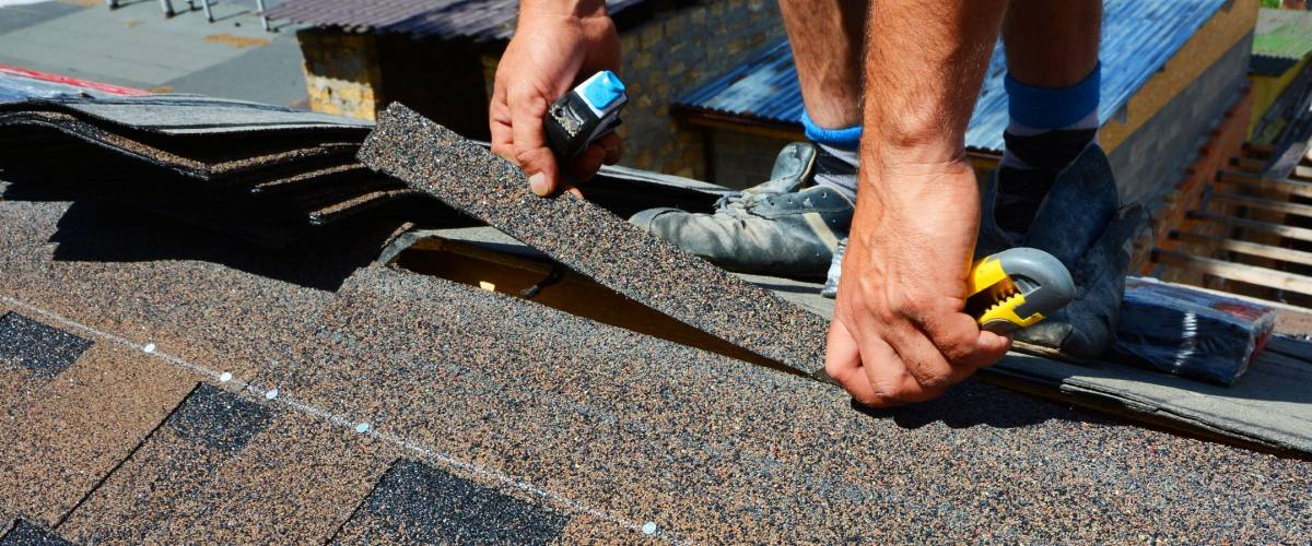 Repairing of roof by cutting felt or bitumen shingles during waterproofing works.