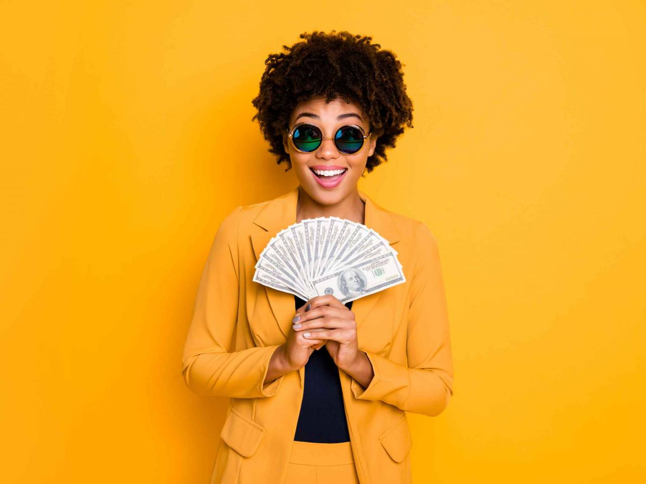 woman on yellow background holding cash