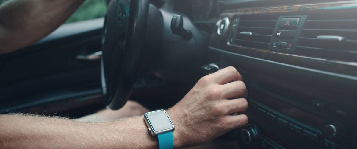 Man driving a car and tuning radio, smart watch on the hand