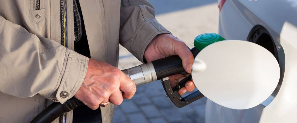 Senior male hands inserting fuel nozzle in car for gasoline fueling