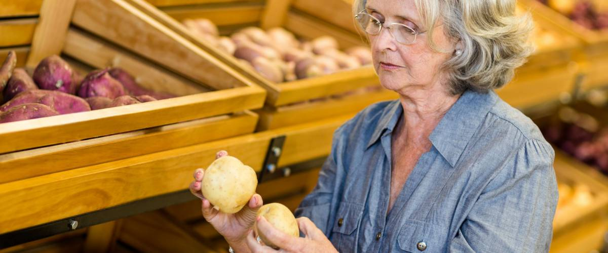 Senior woman holding potatoes at the grocery shop