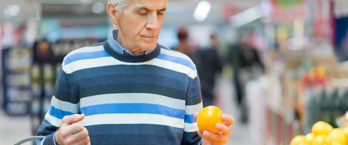 Senior man choosing fruit to buy at supermarket