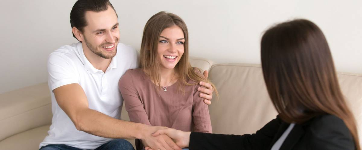 Cheerful happy young couple purchasing apartment.