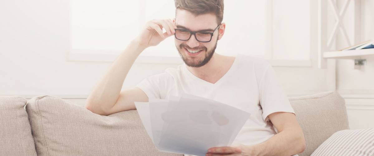 Happy young businessman reading documents. Man working at home on couch, copy space
