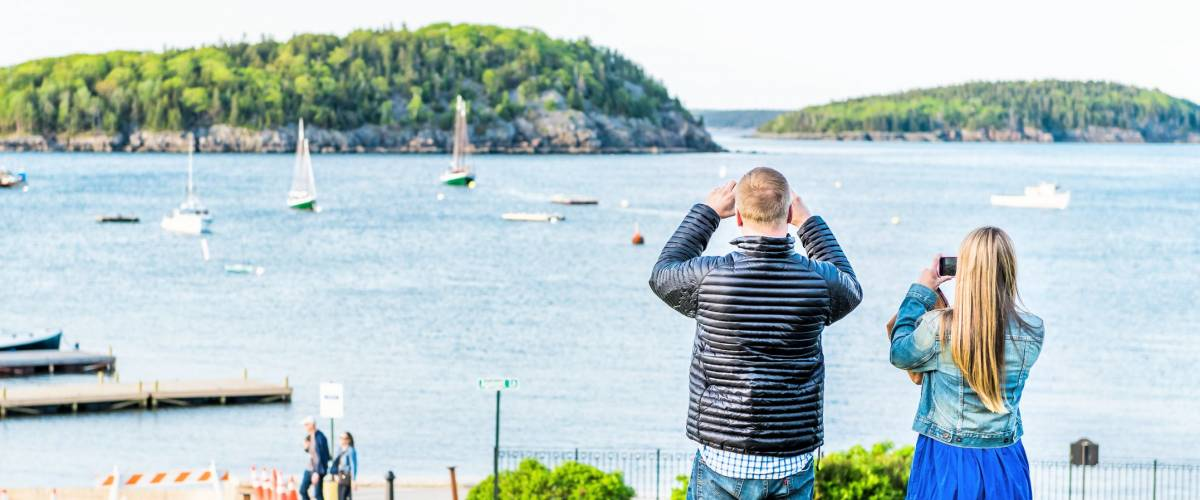 Bar Harbor, USA - June 8, 2017: Young couple, man, woman taking pictures using smartphone, mobile phone on green grass hill in park downtown village in summer by boats