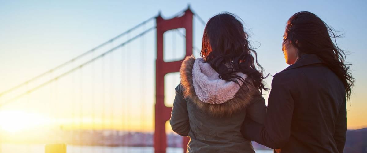 same sex female couple with pet shiba inu watching sunrise at the golden gate bridge