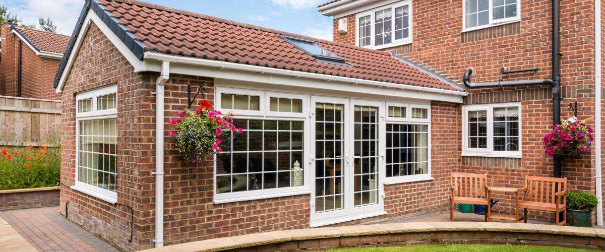 Modern Sunroom external / Modern Sunroom or conservatory extending into the garden, surrounded by a block paved patio
