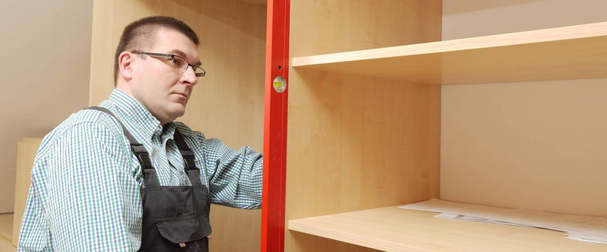 Carpenter assembling wardrobe furniture in walk-in closet