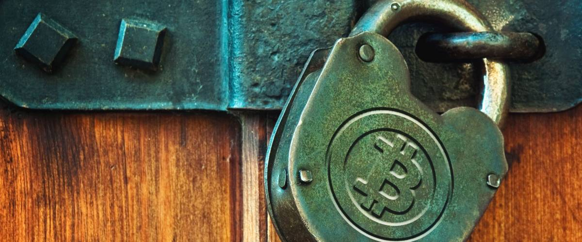 Bitcoin currency symbol on old metal padlock, safety concept.