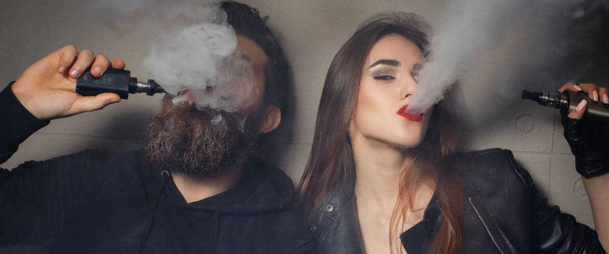 Concept of smoking in public places is steam and smoke. Couple vaping. Vape addiction concept.