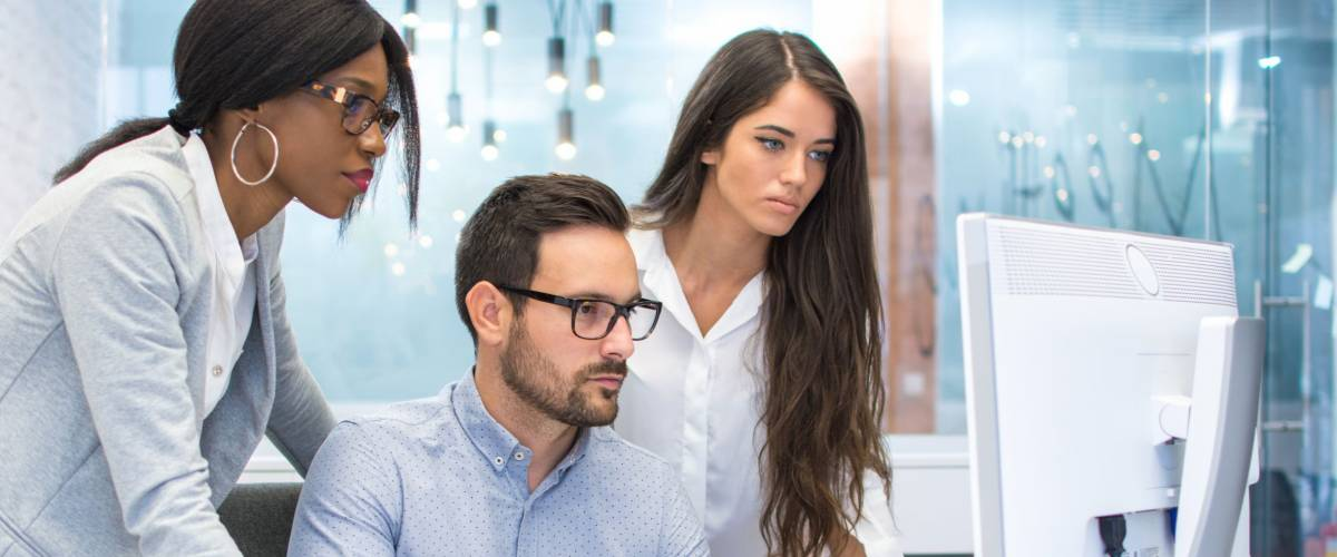 Concerned business people looking at financial report on computer screen at office