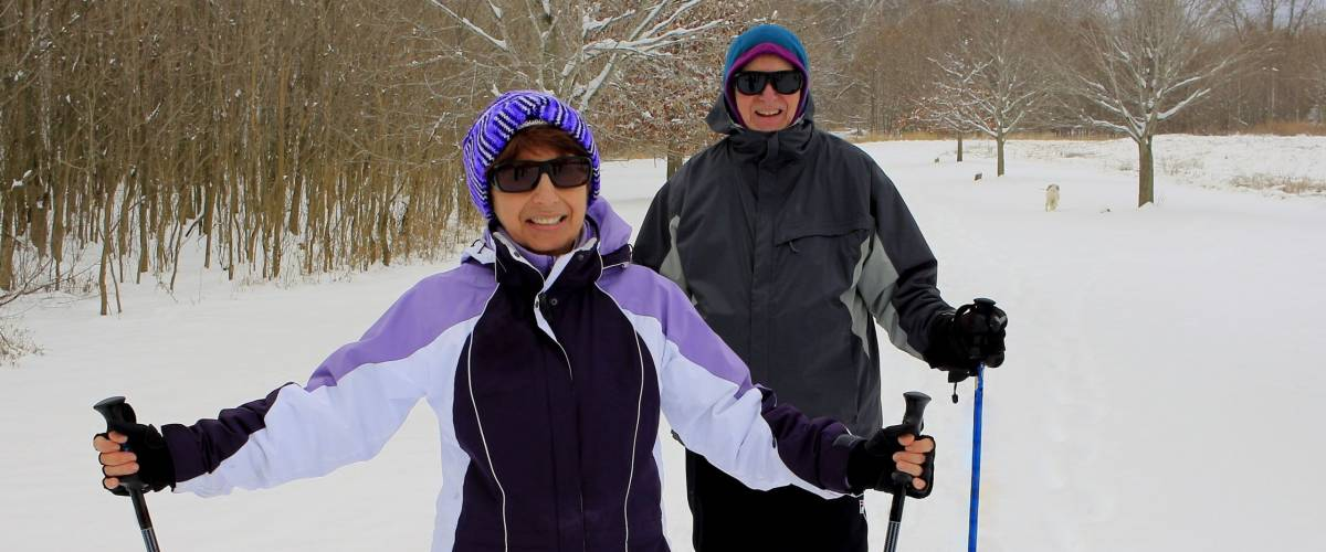 Senior couple skiing cross-country in the field