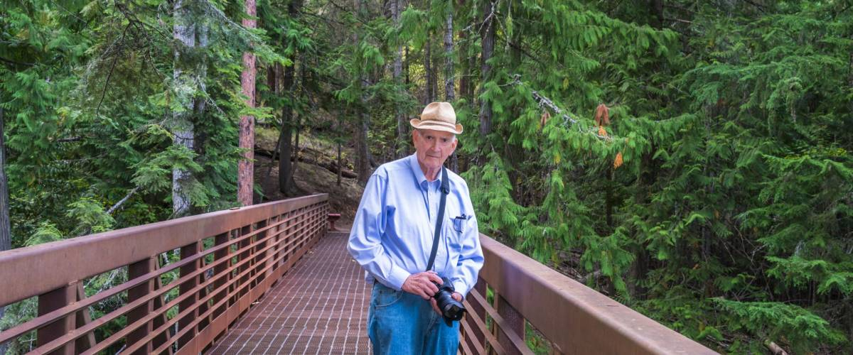 Healthy Active Senior Photographer Hiking Outdoors. Copy space.