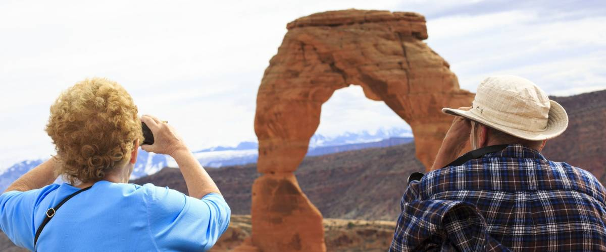 Seniors couple enjoying the beauty of Delicate Arch, Utah, USA