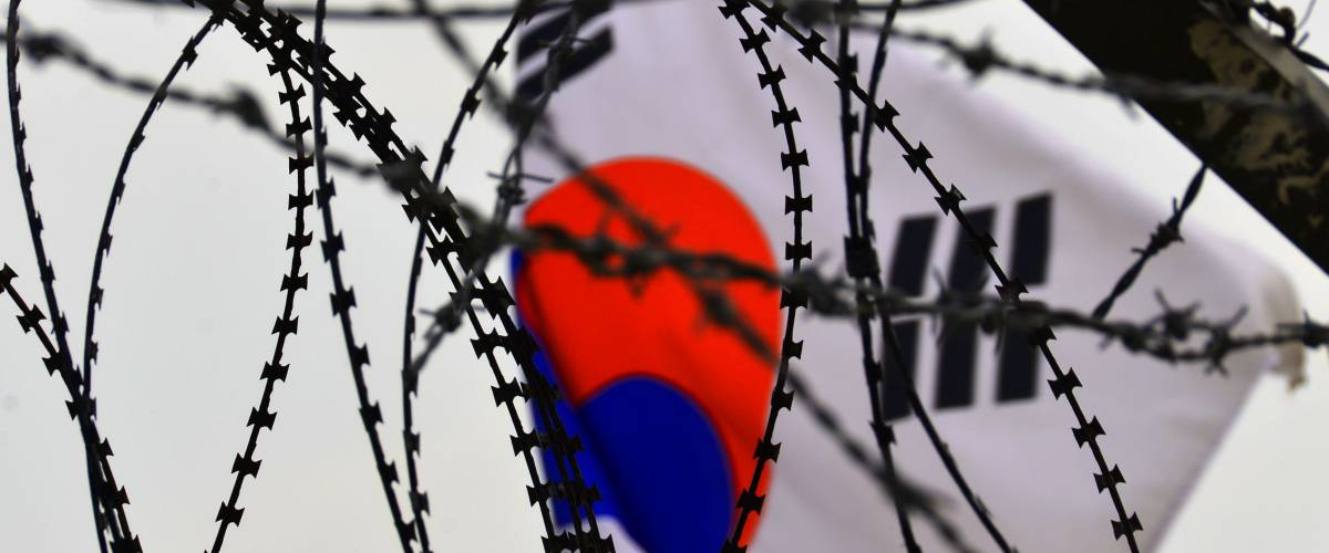 Fence and flag at the Korean Demilitarized Zone is a strip of land running across the Korean Peninsula that serves as a buffer zone between North & South Korea