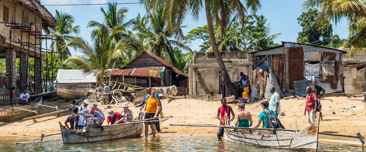 AMBATOZAVAVY, NOSY BE, MADAGASCAR - DECEMBER 19, 2015: Tourists take places on the traditional wood pirogue with outrigger in the Ambatozavavy village on the island of Nosy Be, Madagascar.