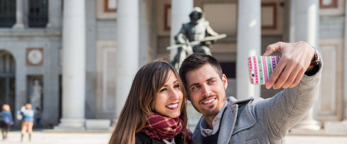 Couple of tourists, a man and a woman, taking selfie in front of prado museum, in the city of Madrid, Spain