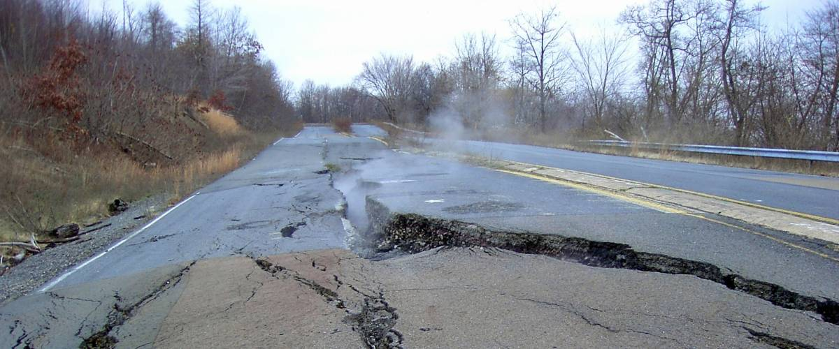 Smoke rising out of cracks in the pavement in Centralia, Pennsylvania