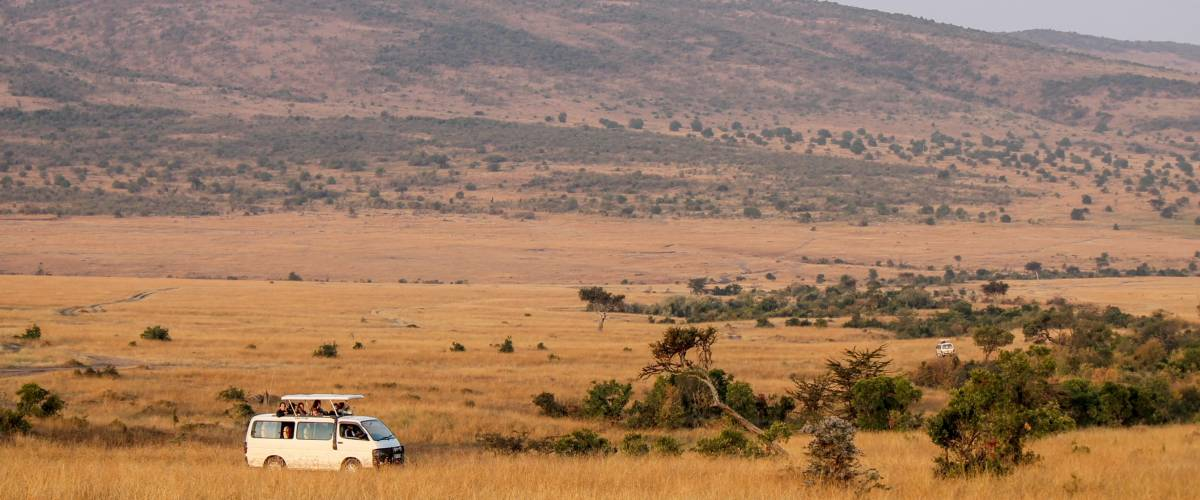 MAASAI MARA NATIONAL RESERVE, KENYA, AFRICA - 2016. Safari Van filled with Eco Tourists Driving Through the Valley