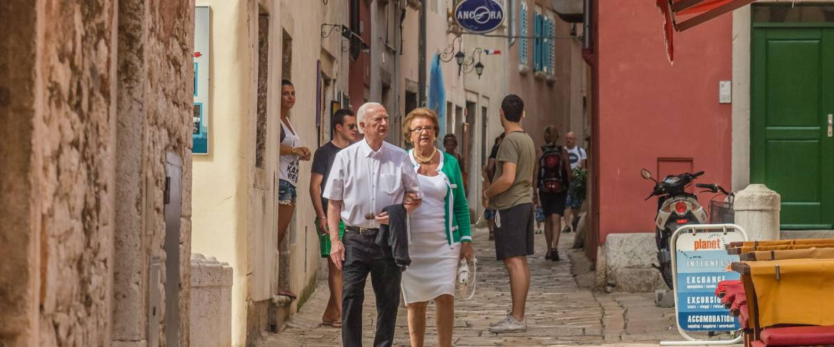 ROVINJ, ISTRIA PENINSULA, CROATIA - may 2018: cityscape. elderly couple walking charming narrow stone street in historical center of Rovinj, Croatia
