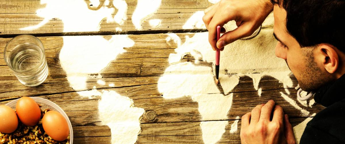 Drawing maps of the world with flour. Artist holding a brush in his hand and draw on old wood