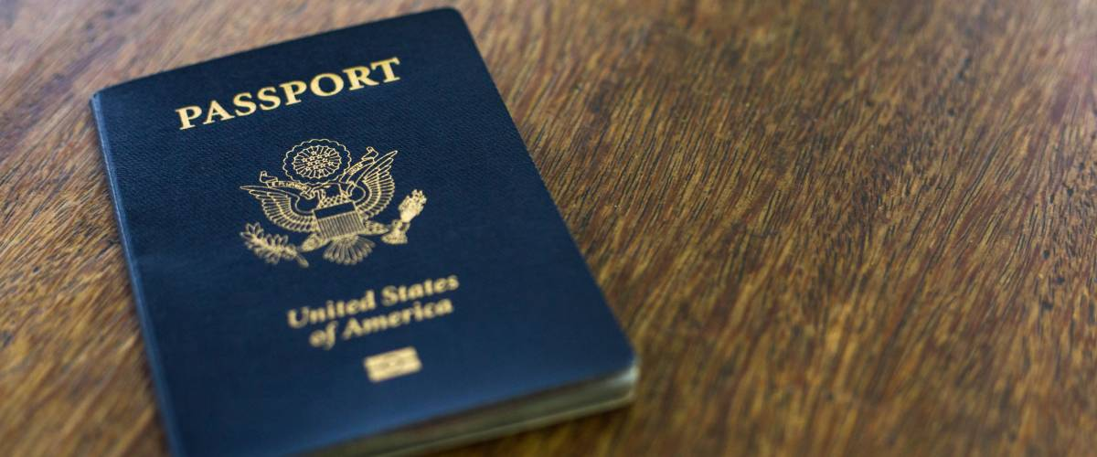 One American passport on a wooden table